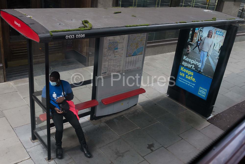 With a further 89 UK covid victims in the last 24hrs, bringing the total victims to 43,995 during the Coronavirus pandemic, a man wearing social distance t-shirt worn by railway station concourse employees, sits at a bus stop next to an ad urging Londoners to stay apart, on 2nd July 2020, in London, England.