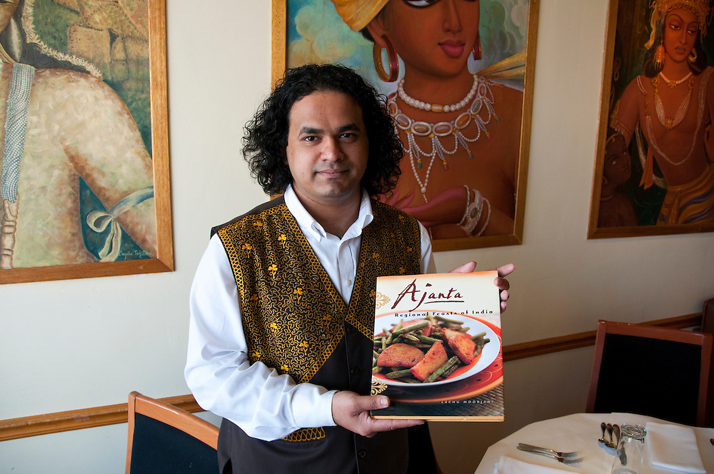 Berkeley, California: Ajanta Indian Restaurant manager Bryan Desouza with cookbook.  Photo copyright Lee Foster.  Photo # california123465