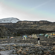 Tents at Moir Hut Camp (13,660 feet) on Mt Kilimanjaro's Lemosho Route. The mountain peak, covered in snow, is in the distance at left.