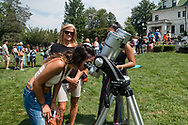 Middletown, New York - A woman looks at the partial solar eclipse through binoculars with solar filters on Alumni Green at SUNY Orange on Aug. 21, 2017.