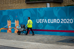 © Licensed to London News Pictures. 10/06/2021. LONDON, UK.  A workman installing signage around Wembley Stadium for the upcoming 2020 UEFA European Football Championship, commonly known as Euro 2020.  The tournament was postponed from 2020 due to the COVID-19 pandemic in Europe and rescheduled for 11 June to 11 July 2021 with matches to be played in 11 cities in 11 UEFA countries.  Wembley Stadium will host certain group matches including England v Croatia on 13 June, as well as the semi-finals and final itself.  Photo credit: Stephen Chung/LNP