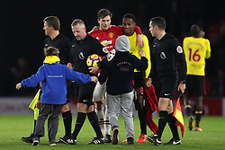 A couple of young fans make it onto the pitch after the final whistle during the Premier League match at Vicarage Road, Watford.