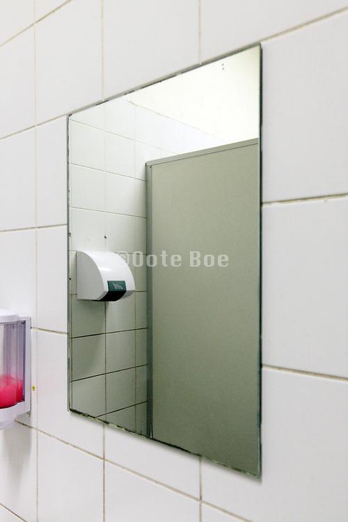 mirror and soap dispenser in a public bathroom