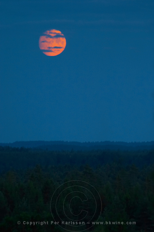Full moon on a dark blue night sky partially obscured by clouds. Smaland region. Sweden, Europe.