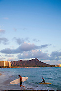 Surfers coming out of the water at sunset on Waikiki Beach, Oahu, Hawaii with Diamond Head in the distance