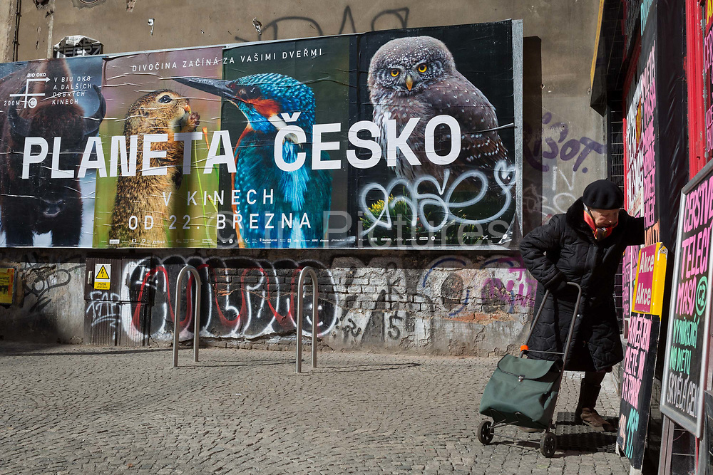 An elderly lady enters a shop beneath a billboard ad announcing a forthcoming TV series about nature and wildlife in the Czech Republic, on Milady Horakove street, Holesovice district, Prague 7, on 20th March, 2018, in Prague, the Czech Republic.