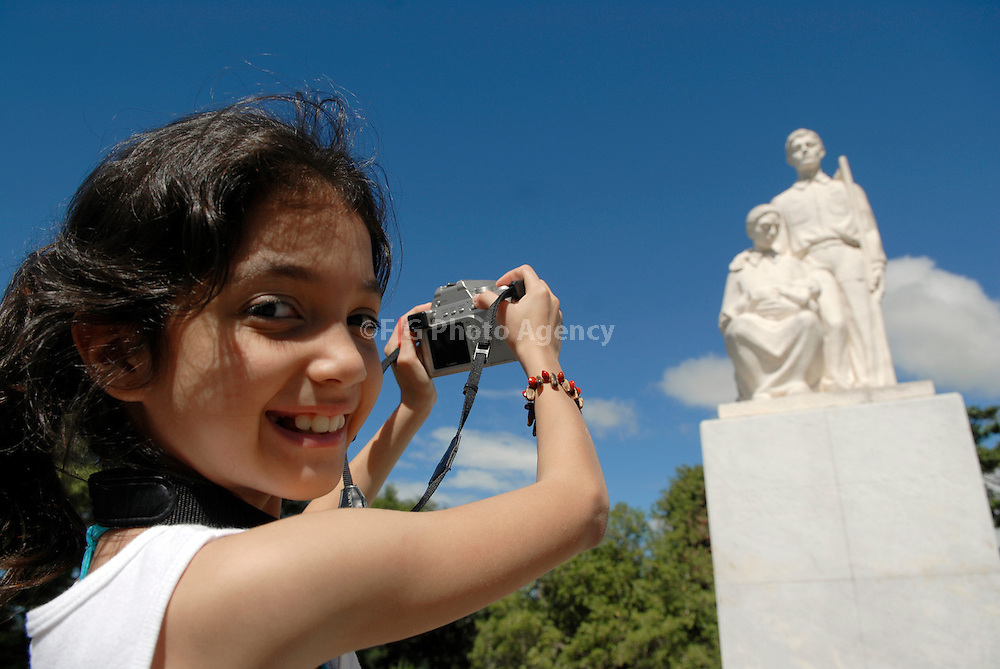 """2007/10/21-Cayey, Puerto Rico-Monument to the Puerto Rican farmer, also known as """"Jibaro"""". A young girl take pictures of the statue during a trip around the island."""