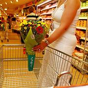 NLD/Huizen/20050713 - Supermarkt Supercoop heeft aan de winkelwagen een houder voor een bosje bloemen gemonteerd..winkelkar, winkelen, gemak,