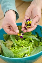 Sarah adding edible viola flowers to a bowl of salad