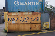 A Hand car Wash business in a London backstreet. This urban landscape is on a dull day in flat light, matching ther grey nature of this area of north London where many businesses scratch a living in industrial side streets. A hand-painted name of this business is seen on the gate door with a shipping container with the old company name of Hanjin on the side.