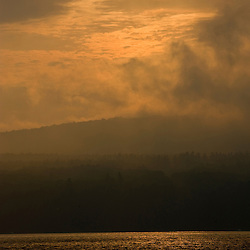 The sun burns through the fog at Lake Sunapee State Beach in Newbury, New Hampshire.