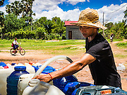 02 JUNE 2016 - SIEM REAP, CAMBODIA: A man fills his water bottles at a public well west of Siem Reap. He said the well near his home had run dry so he made daily trips to the public well to get water for his home. Cambodia is in the second year of  a record shattering drought, brought on by climate change and the El Niño weather pattern. Farmers in the area say this is driest they have ever seen their fields. They said they are planting because they have no choice but if they rainy season doesn't come, or if it's like last year's very short rainy season they will lose their crops. Many of the wells in the area have run dry and people are being forced to buy water to meet their domestic needs.    PHOTO BY JACK KURTZ