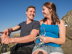 Young couple drinking white wine, Beach of Azkorri, Getxo, Biscay, Spain