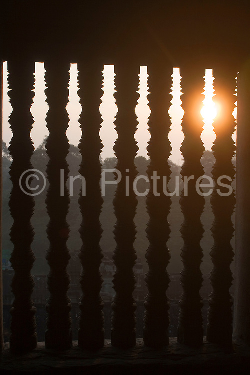Dawn sun shines through the balusters at Angkor Wat. This jewel in the crown of Angkor's ancient temples is a vision of beauty, might and Khmer architectural excellence. The five towers dominate the view, which you are led to trough outer walls, along causeways over the moat and past the two giant pools which act as a mirror of the vision. Consecrated at around 1150 to the Hindu god, Vishnu it is suggested that construction took 30 years.