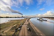Nederland, Nijmegen, 4-2-2015Aan de overkant van de Waal bij Lent wordt druk gewerkt aan het creeren van een 3 km. lange nevengeul in de rivier om bij hoogwater een betere waterafvoer te hebben. Dit zal hier bij de flessenhals Nijmegen 25 tot 30 cm. waterhoogte schelen. Het is een omvangrijk project waarbij onder meer de pijlers van het spoorviaduct een bredere basis moeten krijgen. Ook de n325 die vanaf de Waalbrug noordwaarts loopt moet over 400 meter opnieuw worden aangelegd omdat het talud vervangen wordt door pijlers. Het dorp veurlent komt op een kunstmatig eiland te liggen met twee bruggen als ontsluiting. Een voetgangersbrug en de andere voor normaal verkeer. Een nieuwe kade moet een impuls geven aan evenementen en watersport, pleziervaart. Op de foto de nieuwe situatie in westelijke richting. Ruimte voor de rivier, water, waal. In de nieuwe dijk wordt een drempel gebouwd die stapsgewijs water doorlaat en bij hoogwater overloopt. Measures taken by Nijmegen to give the river Waal, Rhine, more space to flow during highwater and to prevent the risk of flooding. Room for the river. Reducing the level, waterlevel. Foto: Flip Franssen/Hollandse Hoogte