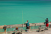 A fisherman waits for a catch on the pier at Folly Beach , SC.