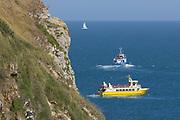 Tour boats along the Jurassic Coast World heritage Site near Dancing Ledge, Dorset, UK.