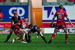 Scarlets' Ioan Nicholas is tackled by Dragons' Cory Hill and Dan Babos<br /> <br /> Photographer Craig Thomas/Replay Images<br /> <br /> Guinness PRO14 Round 13 - Scarlets v Dragons - Friday 5th January 2018 - Parc Y Scarlets - Llanelli<br /> <br /> World Copyright © Replay Images . All rights reserved. info@replayimages.co.uk - http://replayimages.co.uk