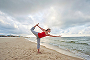 A woman practices yoga at sunrise on the beach in Alabama.