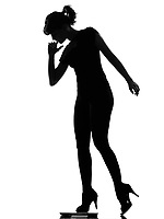 full length silhouette in shadow of a young woman stepping on personal bathroom weight scale  in studio on white background isolated