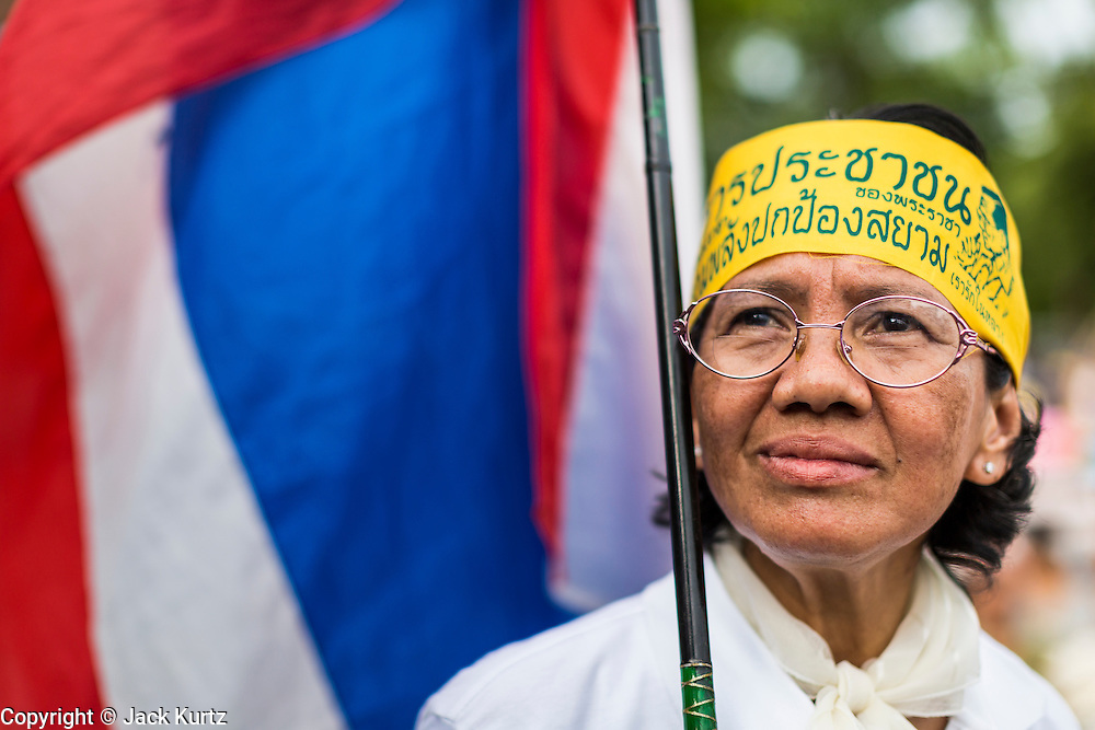 04 AUGUST 2013 - BANGKOK, THAILAND: An anti-government protester with a head band supporting Bhumibol Adulyadej, the King of Thailand, carries a Thai flag during a rally in Bangkok. The protesters are strong supporters of the Thai monarchy. About 2,000 people, members of the  People's Army against Thaksin Regime, a new anti-government group, protested in Lumpini Park in central Bangkok. The protest was peaceful but more militant protests are expected later in the week when the Parliament is expected to debate an amnesty bill which could allow Thaksin Shinawatra, the exiled former Prime Minister, to return to Thailand.      PHOTO BY JACK KURTZ