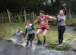 **EXCLUSIVE** ©  London News Pictures. 02/11/2013.  L-R Amy Orange, Sam Cooke (Man U footballer Chris Smalling's girlfriend),  Joel Hicks (dressed as a woman)  and Louise Quartey-Papafio jump into one of the freezing mud ponds together. Wives and girlfriends of Premiership football players do part of the famous Tough Guy event in Wolverhampton, UK. Mandatory photo credit : Mike King/LNP
