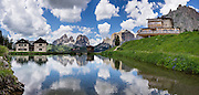 A pond reflects Hotel Gonzaga and peaks of the Langkofel Group (Sassolungo, 3181 meters / 10,436 feet) and Sella Group, in Val di Fassa, 2 km west of Passo Pordoi, in the Dolomites, Trentino-Alto Adige/Südtirol region, Italy. We highly recommend lodging in a pristine, roomy apartment with full kitchen in a beautiful setting at Hotel Gonzaga Appartamenti Garni (Canazei, I-38032, Streda de Pordoi, 102, telephone +39 0462 602121). The Dolomites are part of the Southern Limestone Alps, Europe. UNESCO honored the Dolomites as a natural World Heritage Site in 2009. This panorama was stitched from 6 overlapping photos.