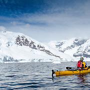 A solo kayakers navigating the waters of Neko Harbour, Antarctica.