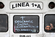 """ORG XMIT: TXDAM110 From inside a bus, family and friends watch the procession of hearses as six of the teenage victims from the weekend shootings are laid to rest in the Villas de Salvarcar neighborhood of Ciudad Juarez, Mexico on Wednesday, Feb. 3, 2010.  The window reads """"Rest in Peace"""".  (Courtney Perry/The Dallas Morning News). 03072010xNEWS"""