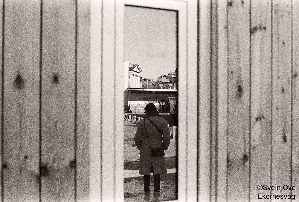 Refleksjoner av ei kvinne og Ålesund i et vindu på cruiseterminalen på Storneskaia.<br /> Foto: Svein Ove Ekornesvåg
