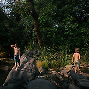 Two brothers walk near a river.
