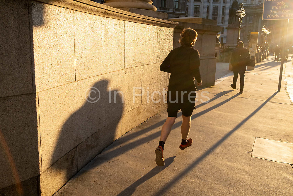 With most Londoners still working from home, a runner leaves his shadow on a wall of Royal Exchange while walking along a quiet Threadneedle Street during the evening rush-hour during the third lockdown of the Coronavirus in the City of London, the capitals financial district, on 26th February 2021, in London, England.