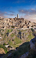"""Long view across """"la Gravina"""" ravine to the Sassi of Matera at sunrise, Basilicata, Italy. A UNESCO World Heritage site.<br /> <br /> The area of Matera has been occupied since the Palaeolithic (10th millennium BC) making it one of the oldest continually inhabited settlements in the world. <br /> The town of Matera was founded by the Roman Lucius Caecilius Metellus in 251 BC and remained a Roman town until  was conquered by the Lombards In AD 664 becoming part of the Duchy of Benevento.  Matera was subject to the power struggles of southern Italy coming under the rule of the Byzantine Roman, the Germans and finally Matera was ruled by the Normans from 1043 until the Aragonese took possession in the 15th century. <br /> <br /> At the ancient heart of Matera are cave dwellings known as Sassi. As the fortunes of Matera failed the sassy became slum dwelling and the appalling living conditions became be the disgrace of Italy. From the 1970's families were forcibly removed from the Sassi and rehoused in the new town of Matera. Today tourism has regenerated Matera and the sassi have been modernised and are lived in again making them probably the longest inhabited houses in the world dating back 9000 years."""
