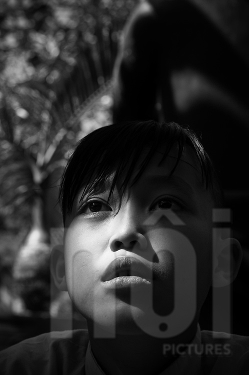Portraiture of a young buddhist monk in a pagoda of Khanh Hoa province, Vietnam, Asia. A ray of sun light is face. He looks away. Feeling of dream