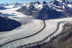 Two large glaciers come together to form the main flow of the McBride Glacier in Glacier Bay National Park and Preserve. The dark lines of rock debris are called medial moraines. A medial moraine is formed when two glaciers meet and the debris on the edges of the adjacent valley sides join and are carried on top of the glacier. <br /> <br /> The McBride Glacier, the most active glacier and only tidewater glacier in the Muir Inlet, is retreating.<br /> <br /> Glacier Bay National Park is located in southeast Alaska. Known for its spectacular tidewater glaciers, icefields, and tall costal mountains, the park is also an important marine wilderness area. The park a popular destination for cruise ships, is also known for its sea kayaking and wildlife viewing opportunities. <br /> <br /> Glacier Bay National Park is home to humpback whales which feed in the park's protected waters during the summer, both black and grizzly bears, moose, wolves, sea otters, harbor seals, steller's sea lions and numerous species of sea birds. <br /> <br /> The dynamically changing park, known for its large, contiguous, intact ecosystems, is a United Nations biosphere reserve and a UNESCO World Heritage site.
