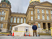"16 MARCH 2020 - DES MOINES, IOWA: An Iowa state employee in front of the Department of Public Health screening tent on the east side of the State Capitol in Des Moines. Because of numerous reports of Coronavirus in Iowa, the governor is suspending the legislative session for 30 days. It was scheduled to run until mid-April. Sunday night, the Governor announced that the state health department had recorded ""community spread"" in Des Moines. As a result the State Capitol instituted mitigation measures that included mandatory health screening for everyone going into the building, canceling group tours of the building, and closing the souvenir shop and snack bar.      PHOTO BY JACK KURTZ"