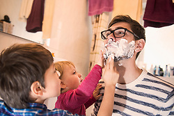 Sons lathering their father for shaving, Munich, Germany