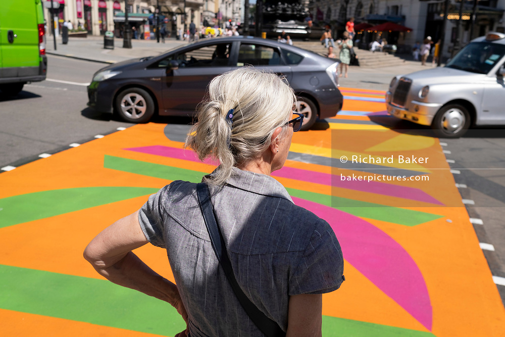 As traffic passes-by, a white-haired woman waits to cross the road, over the multi-coloured markings of a crossing at Piccadilly Circus, on 16th July 2021, in London, England.