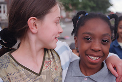 Two primary school girls standing in playground with arms around each other smiling,