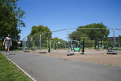 © Licensed to London News Pictures. 23/06/2020. London, UK. A woman walks past an outdoor gym in Chestnuts Park, north London, which has been closed and fenced since 23 March following the COVID-19 lockdown. Outdoor gym will re-open from 4 July as Prime Minister Boris Johnson outlines the plans to restore normal life after three months of coronavirus lockdown. Photo credit: Dinendra Haria/LNP