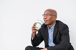 African businessman sitting drinking Coffee to go