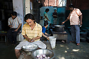 Nasir a young chef chops onions in front of the kitchen at Babu Shahi Bawarchi, New Delhi, India<br /> The famous but modest takeaway housed in the grounds of a shrine is famous for its biryani and whose owners ancestors served as chief cooks under the Moghul Emperor, Shah Jahan
