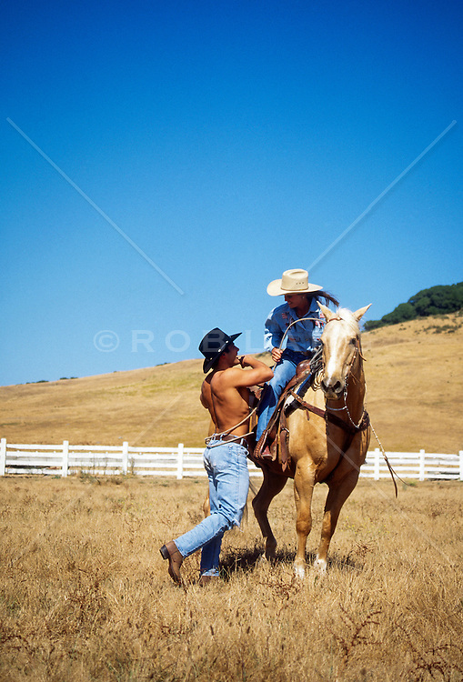 cowgirl roping in a shirtless cowboy on a ranch