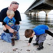 """Keith Heller, of Ridgeland, helps his grandson Ayden Fillinger, 2, of Columbia, put his boot back on after Ayden thought their was a crab inside of it, meanwhile grandson Gabryl,3, right, digs through the sand underneath the Broadriver Bridge on Lemon Island on December 28, 2014.  """"We're here to burn some energy... Figured it would be the best place to turn them loose,"""" said Heller."""