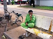A sanitation work takes a break from sweeping trash. She inhales the fragrant scent of a jasmine garland.