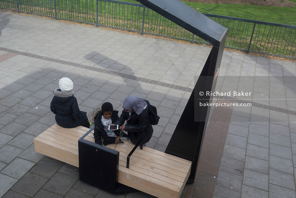 A Muslim family use a pavement shelter, on 23rd March 2019, in London, England.