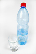 Cutout of a Plastic Bottle and glass of Mineral Water on white background