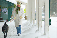 A young woman walks with her dog along a snowy sidewalk in Jackson, Wyoming.