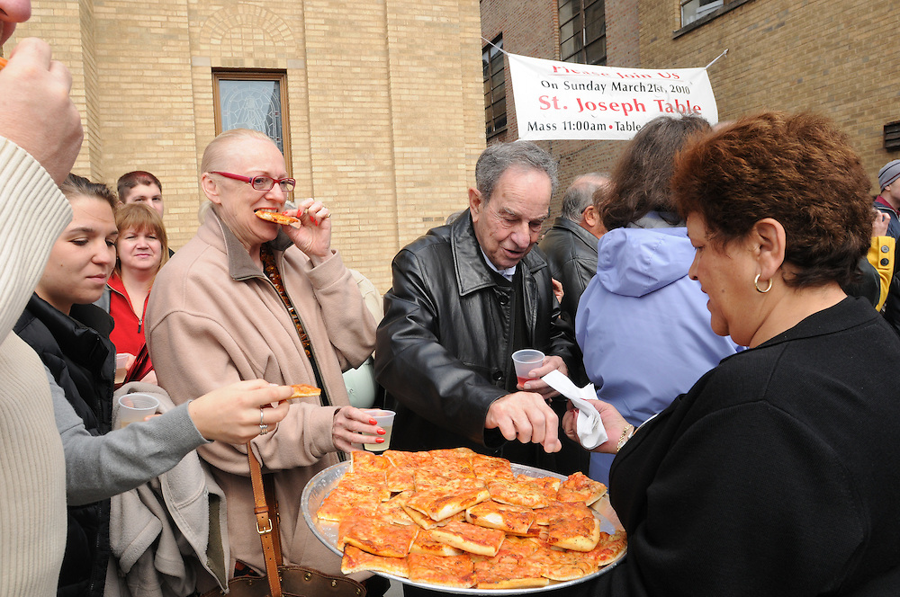 Parishioners at Our Lady of Pompeii Catholic Church enjoy slices of fresh pizza while in line to celebrate St. Joseph's Bountiful Table in the parish hall. The annual Italian feast commemorates the end of drought and famine following the prayers of hungry Sicilians to Saint Joseph the Protector.