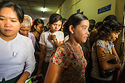 """17 JUNE 2013 - YANGON, MYANMAR:   Passengers in Yangon wait to board the Dala bound Yangon-Dala ferry. The ferry to Dala opposite Yangon on the Yangon River is the main form of transportation across the river. Every day the ferry moves tens of thousands of people across the river. Many working class Burmese live in Dala and work in Yangon. The ferry is also popular with tourists who want to experience the """"real"""" Myanmar. The rides takes about 15 minutes. Burmese pay about the equivalent of .06¢ US for a ticket.  Foreigners pay about the equivalent of about $4.50 US for the same ticket.    PHOTO BY JACK KURTZ"""